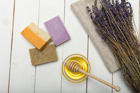 Close-up view of homemade soap collection with dried lavender flowers and honey