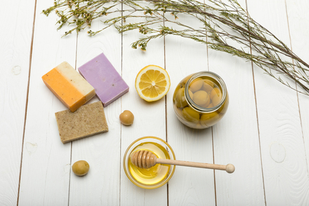 Top view of handmade soap with lemon, olives and honey on wooden table top Stock Photo