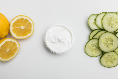 Top view of facial cream in container, cucumber and lemon slices isolated on grey