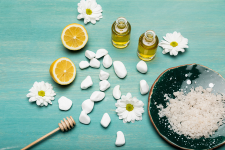Top view of sea salt, oil in bottles, sliced lemon and chamomiles on wooden table top Stock Photo