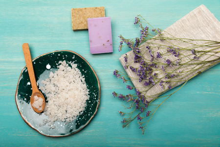 Top view of dried lavender flowers with sea salt and handmade soap on blue wooden surface