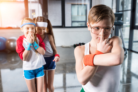 adorable kids in sportswear fooling around at fitness studio