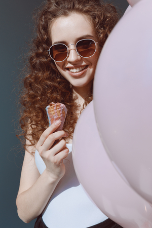 beautiful red hair girl in sunglasses eating ice cream and holding air balloons