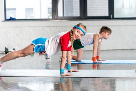 サイドビューのスポーティな男の子と女の子、腕立て伏せスポーツウェアにジムでパワーアップ