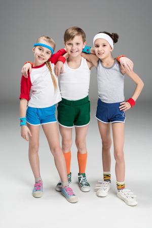 Adorable, souriant, sportif, enfants, sportswear, debout, ensemble, isolé, gris Banque d'images