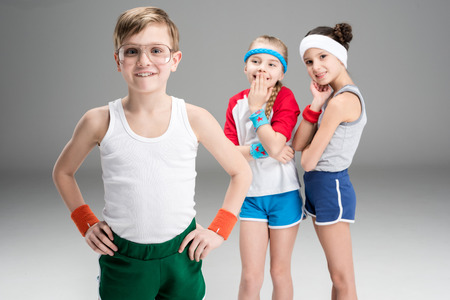Cute smiling sporty girls looking at happy boy in sportswear