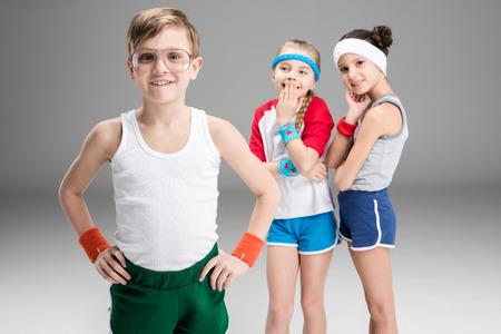 Leuke glimlachende sportieve meisjes die gelukkige jongen in sportkleding bekijken