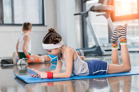 Side view of little girl in earphones lying on yoga mat and using smartphone in gym