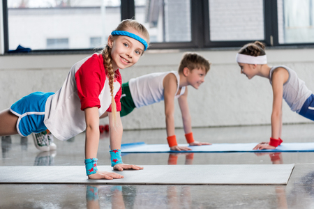Cute sporty kids exercising on yoga mats in gym and smiling