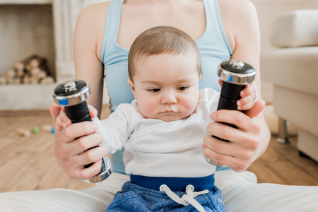 woman and baby boy playing with dumbbells at home