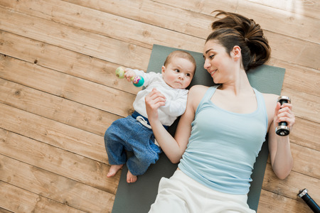 mother with baby boy lying on floor and playing with dumbbells Standard-Bild