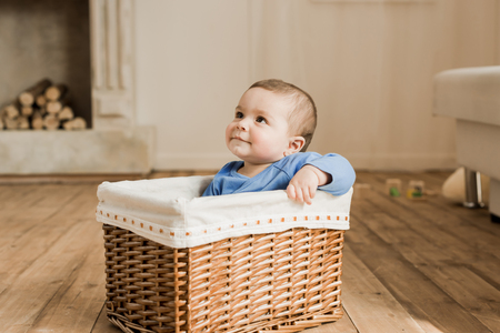 smiling little baby boy sitting inside of braided box and looking aside at home Stock fotó