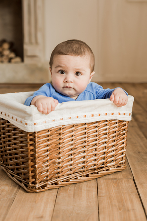 Portrait of adorable little baby boy sitting inside of braided box