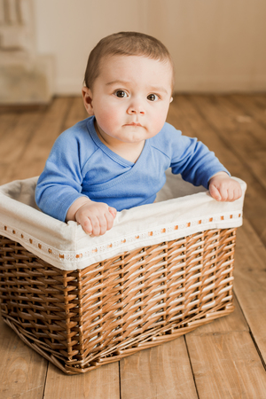 cute little baby boy sitting inside of braided box and looking at camera