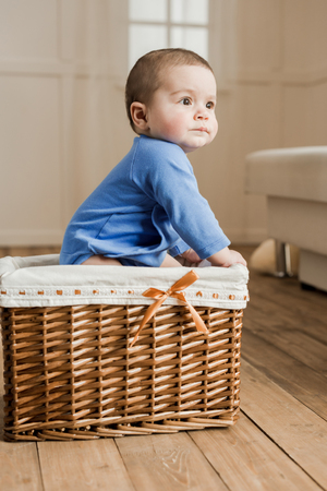 cute little baby boy sitting inside of braided box at home
