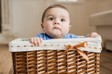 adorable baby boy sitting inside of brown braided box
