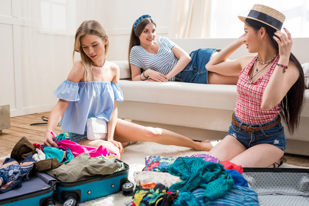 overfilled: young women packing suitcases for vacation together at home, getting ready to travel concept