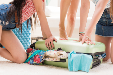 women packing suitcase for vacation together at home, packing luggage concept Stock Photo