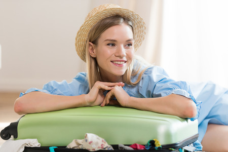 Smiling young blonde woman in hat packing suitcase and looking away