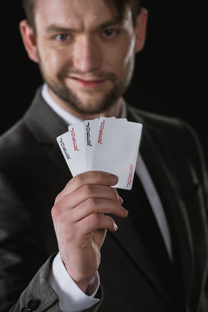 businessman holding Joker cards in hand isolated on black Stock Photo