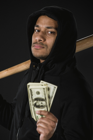 robber in zoodie with baseball bat and money isolated on black