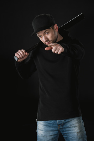robber in zoodie and cap with baseball bat isolated on black 版權商用圖片