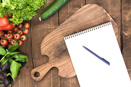 organic vegetables, chopping board and blank notepad with pen on wooden background