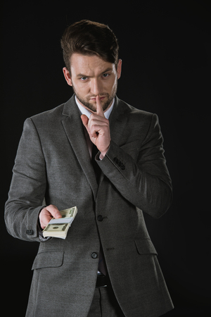 businessman with hush gesture holding dollar banknotes isolated on black