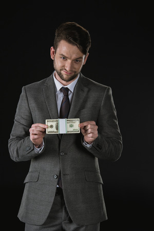 corrupt: businessman holding dollar banknotes isolated on black Stock Photo