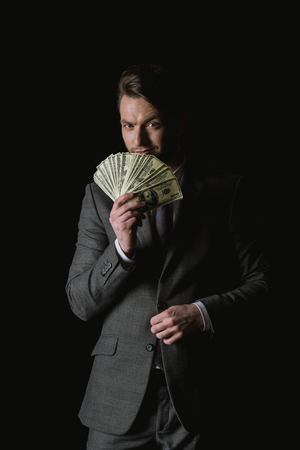 businessman holding dollar banknotes fan isolated on black