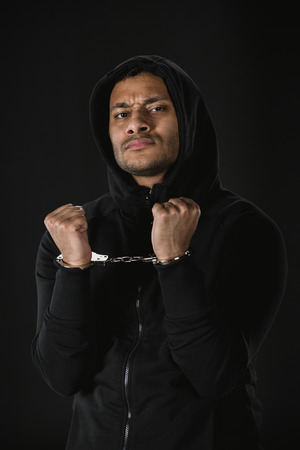 zoodie と黒に分離されて手錠でアフリカ系アメリカ人の強盗 写真素材