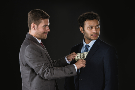 Businessman giving money and bribing business partner