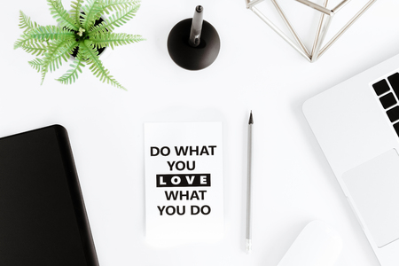 Top view of do what you love, love what you do motivational quote and laptop at workplace