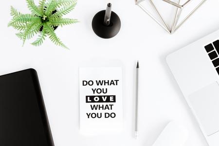 Vista superior de hacer lo que amas, amar lo que haces cita motivacional y portátil en el lugar de trabajo Foto de archivo - 80059725