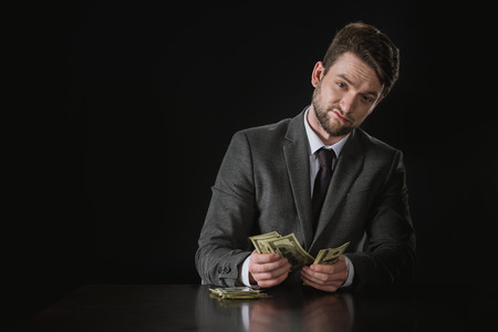 portrait of confident businessman sitting at table and counting money