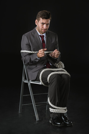 upset businessman roped on to chair isolated on black