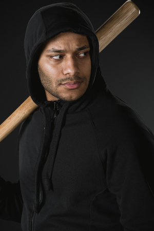 african american robber in zoodie with baseball bat isolated on black