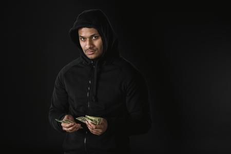 黒に分離されてお金を保持している zoodie のアフリカ系アメリカ人の強盗