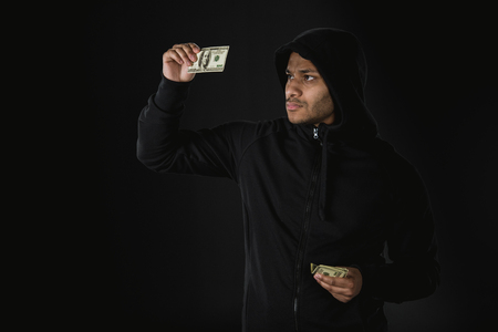african american robber in zoodie holding money isolated on black