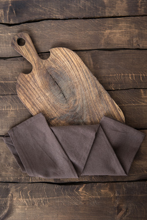 old scratched chopping board with brown napkin on the table