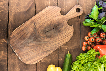 eating utensil: vegetables and greens with wooden cutting board. Healthy food background