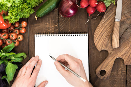 Food composition of raw vegetables, chopping board and human hand able to write something in notepad