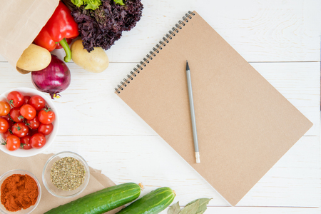 notebook and pencil with fresh raw vegetables on wooden table Zdjęcie Seryjne