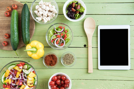 Top view of fresh raw vegetables and salads in bowls and digital tablet