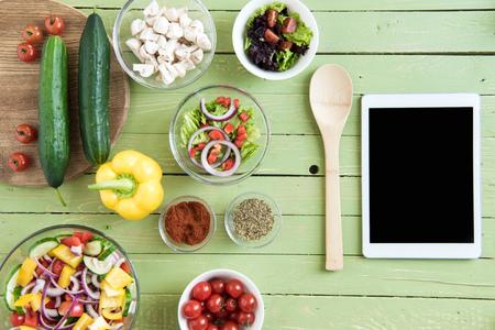 Vista superior de verduras frescas y ensaladas en tazones y tableta digital Foto de archivo - 80150812
