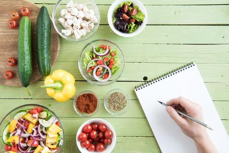 persoon die potlood en het schrijven van recept in kookboek tijdens het koken Stockfoto