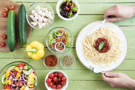 partial: person holding fork and knife while eating spaghetti with sauce and basil and fresh raw vegetables on wooden table Stock Photo