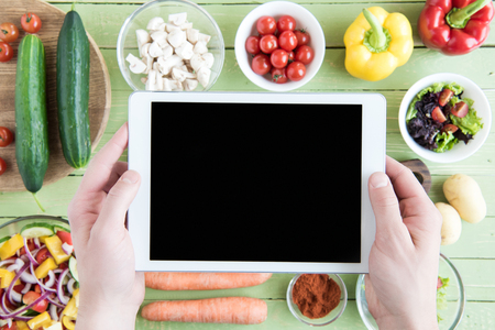 person holding digital tablet with blank screen and raw vegetables on wooden table Stock Photo