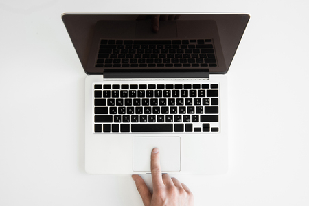 partial: top view of human hand and laptop computer isolated on white