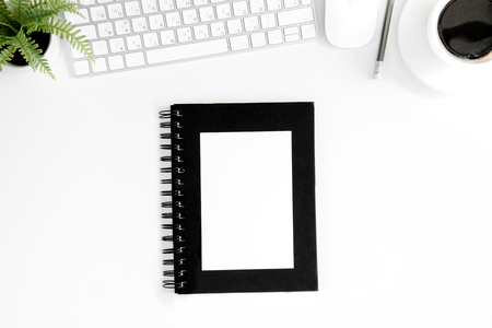 partial: Top view of notebook with blank cover, cup of coffee, computer mouse and keyboard Stock Photo
